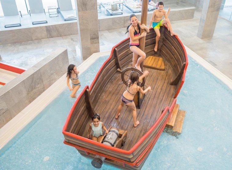 Kinder im Piratenschiff am Pool